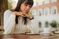 Kvinna som använder den digitala minnestavlan på den utomhus- coffee shop Royaltyfria Foton