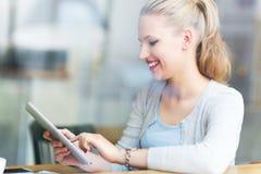 Kvinna som använder den digitala minnestavlan på kafét Arkivbild