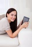 Kvinna som använder den digitala minnestavlan på soffan Royaltyfria Bilder