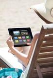 Kvinna som använder den digitala minnestavlan på solstol Arkivbild