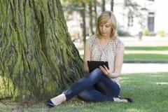 Kvinna som använder den digitala tableten vid treen på lawn arkivbild