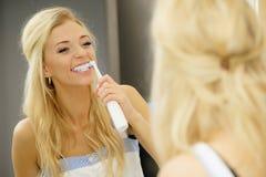 Kvinna som använder den elektriska tandborsten Arkivfoto