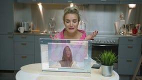 Kvinna som använder den futuristiska datorbildskärmen till video pratstund arkivfilmer