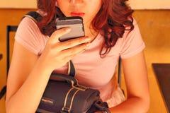 Kvinna som använder den smarta telefonen Arkivfoto