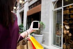 Kvinna som använder den smarta telefonen för att shoppa direktanslutet i shoppinggalleria royaltyfri foto
