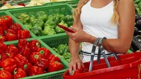 Kvinna som använder den smarta telefonen, medan shoppa på supermarket arkivfilmer