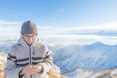 Kvinna som använder den smarta telefonen på bergen Panoramautsikt av snowcapped fjällängar i kall vintersäsong Begrepp av att del arkivbild