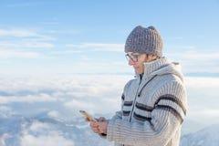 Kvinna som använder den smarta telefonen på bergen Panoramautsikt av snowcapped fjällängar i kall vintersäsong Begrepp av att del arkivfoto