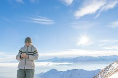 Kvinna som använder den smarta telefonen på bergen Panoramautsikt av snowcapped fjällängar i kall vintersäsong Begrepp av att del royaltyfri fotografi