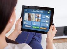 Kvinna som använder det smarta hem- systemet på den Digital minnestavlan arkivfoto
