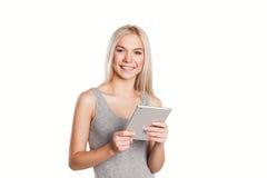 Kvinna som använder digitalt isolerat lyckligt för minnestavladator Arkivfoto