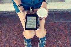 Kvinna som använder digitalt minnestavlasammanträde på bänken som bläddrar internet som dricker kaffe arkivbild