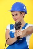 Kvinna som använder drillborren Arkivbilder