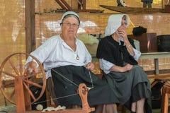 Kvinna som använder en antik snurrmaskin till tråden Fotografering för Bildbyråer
