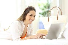 Kvinna som använder en bärbar dator som ser dig på semestrar Royaltyfri Bild
