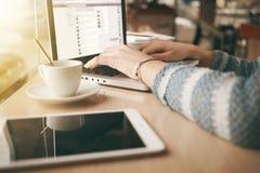 Kvinna som använder en bärbar dator under ett kaffeavbrott royaltyfria bilder