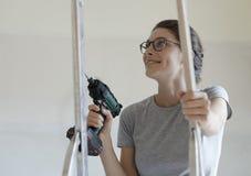 Kvinna som använder en drillborr och ett arbete i hennes nya hus royaltyfria bilder