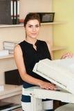 Kvinna som använder en kopieringsmaskin Arkivbild