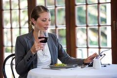 Kvinna som använder en minnestavla och dricker vin royaltyfria foton