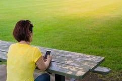 Kvinna som använder en mobiltelefon, medan sitta i en parkera royaltyfri foto