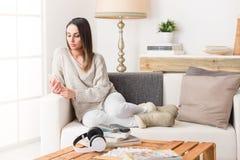 Kvinna som använder en smart telefon på en soffa arkivbilder