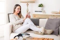 Kvinna som använder en smart telefon på en soffa royaltyfri bild