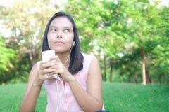 Kvinna som använder en smartphone för att lyssna till musik, medan sitta i ett p Fotografering för Bildbyråer