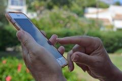 Kvinna som använder en smartphone, finger till pekskärmen arkivbild