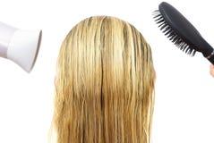 Kvinna som använder hårtork- och hårhårkammen Royaltyfri Foto