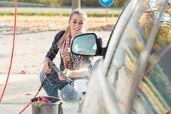 Kvinna som använder högtryckdysan för att göra ren hennes bil royaltyfri bild