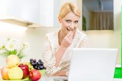 Kvinna som använder henne bärbar datordator i kök Arkivbild
