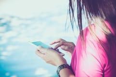 Kvinna som använder henne mobil telefon Fotografering för Bildbyråer