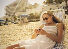 Kvinna som använder henne smartphone på stranden Arkivbild