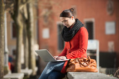 Kvinna som använder hennes bärbar dator i gatan Royaltyfri Fotografi