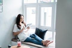 Kvinna som använder hennes grej, medan sitta i kafé royaltyfri foto