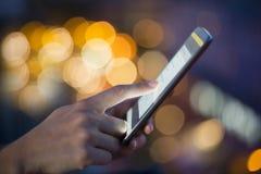 Kvinna som använder hennes mobiltelefon, backgro för ljus för stadshorisontnatt royaltyfri foto