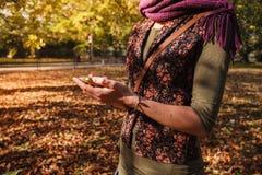 Kvinna som använder hennes telefon i parkera Arkivbild