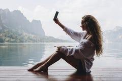 Kvinna som använder hennes telefon vid en sjö fotografering för bildbyråer