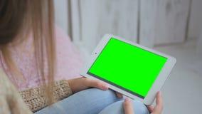 Kvinna som använder horisontalminnestavladatoren med den gröna skärmen Royaltyfri Bild