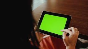 Kvinna som använder horisontalminnestavlan på tabellen grön skärm lager videofilmer