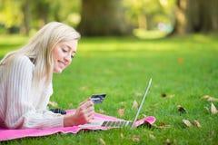 Kvinna som använder kreditkorten som direktanslutet shoppar med en bärbar dator i medeltalen Royaltyfria Foton