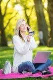 Kvinna som använder kreditkorten som direktanslutet shoppar med en bärbar dator i medeltalen Arkivfoton