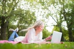 Kvinna som använder kreditkorten som direktanslutet shoppar med en bärbar dator i medeltalen Royaltyfri Foto