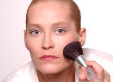 Kvinna som använder makeupborsten Arkivbilder