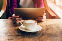 Kvinna som använder minnestavladatoren i coffee shop Royaltyfria Bilder