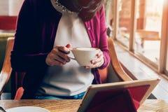 Kvinna som använder minnestavladatoren i coffee shop Arkivfoton