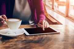 Kvinna som använder minnestavladatoren i coffee shop Arkivbilder