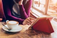 Kvinna som använder minnestavladatoren i coffee shop Royaltyfri Bild