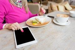 Kvinna som använder minnestavladatoren i kafé Fotografering för Bildbyråer