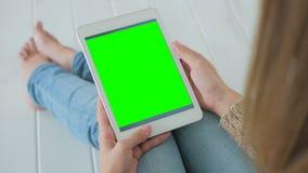 Kvinna som använder minnestavladatoren med den gröna skärmen Royaltyfri Foto